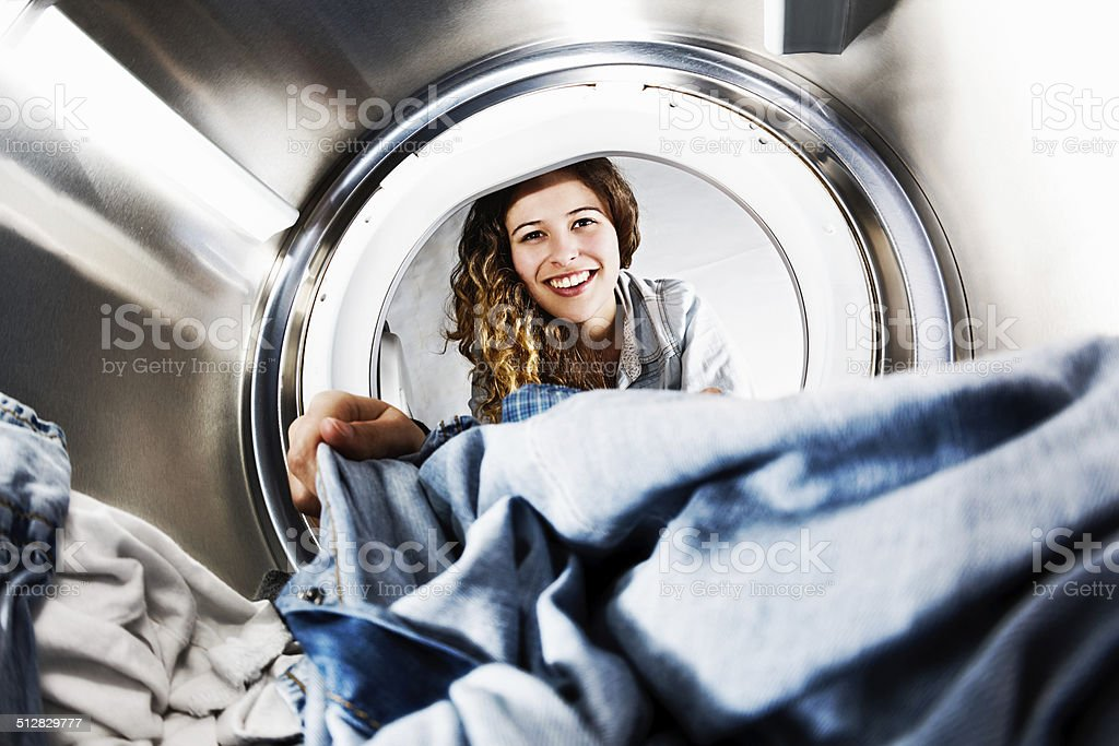 Smiling blonde beauty loads her tumble dryer: seens from inside stock photo