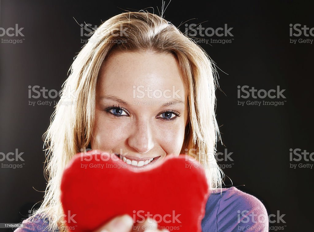 Smiling blonde beauty offers her heart stock photo