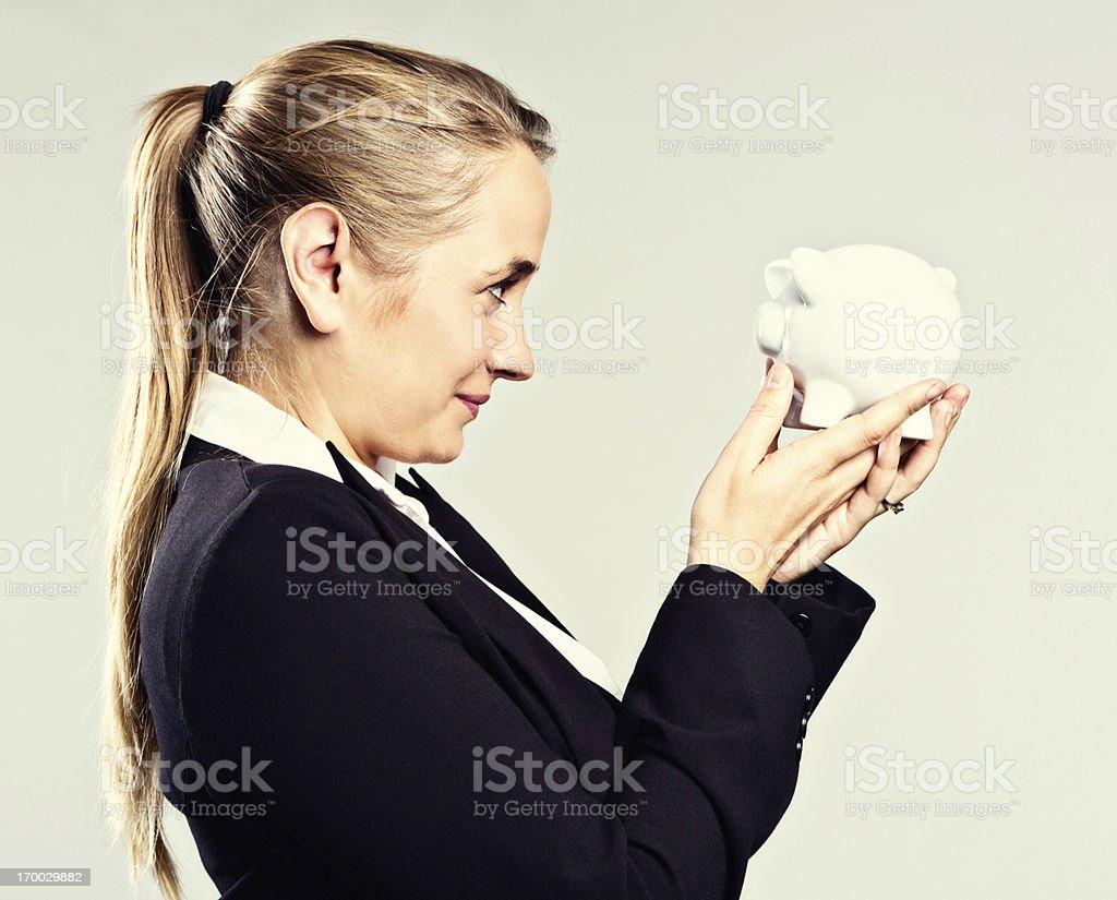 Smiling blonde businesswoman checking savings in piggybank stock photo