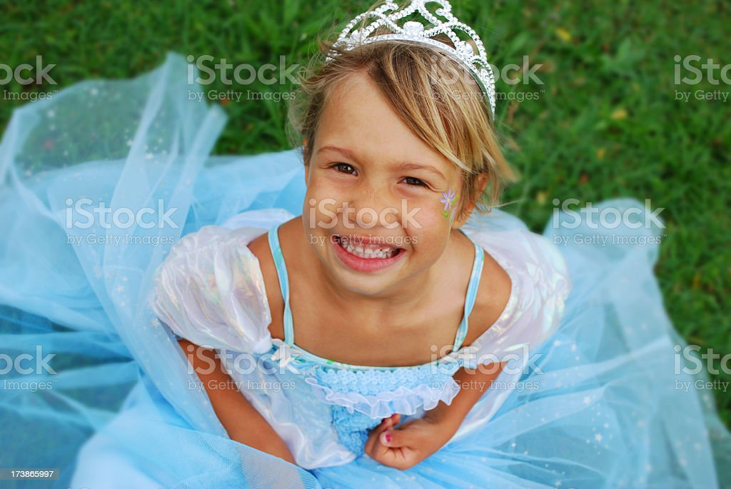 Smiling blonde girl in a bright blue princess dress on grass stock photo