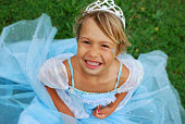 Smiling blonde girl in a bright blue princess dress on grass