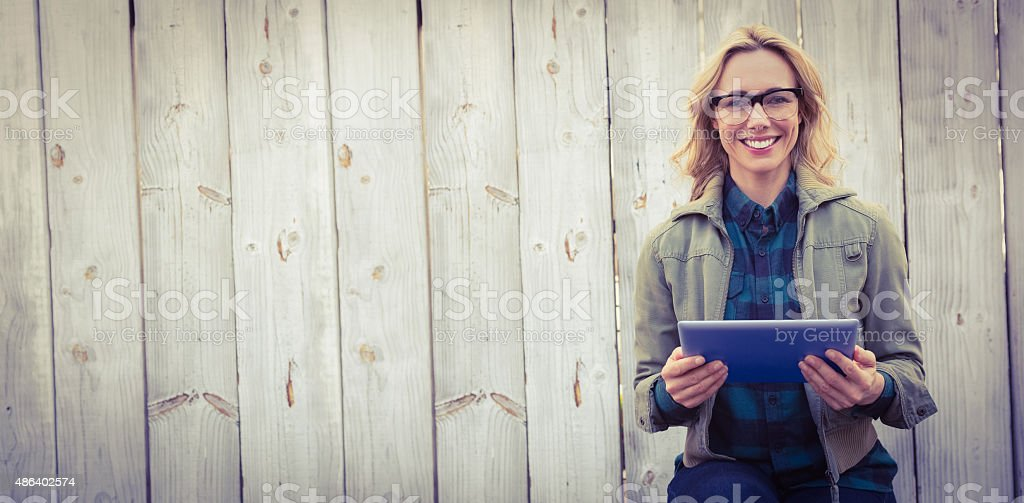 Smiling blonde in glasses using tablet pc stock photo