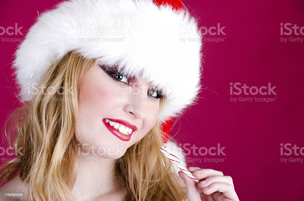 Smiling blonde in Santa hat holding candy cane. royalty-free stock photo