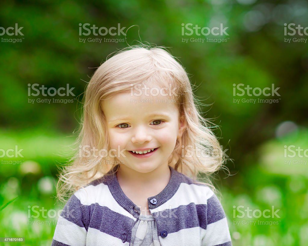 Smiling blonde little girl with curly hair, outdoor portrait royalty-free stock photo