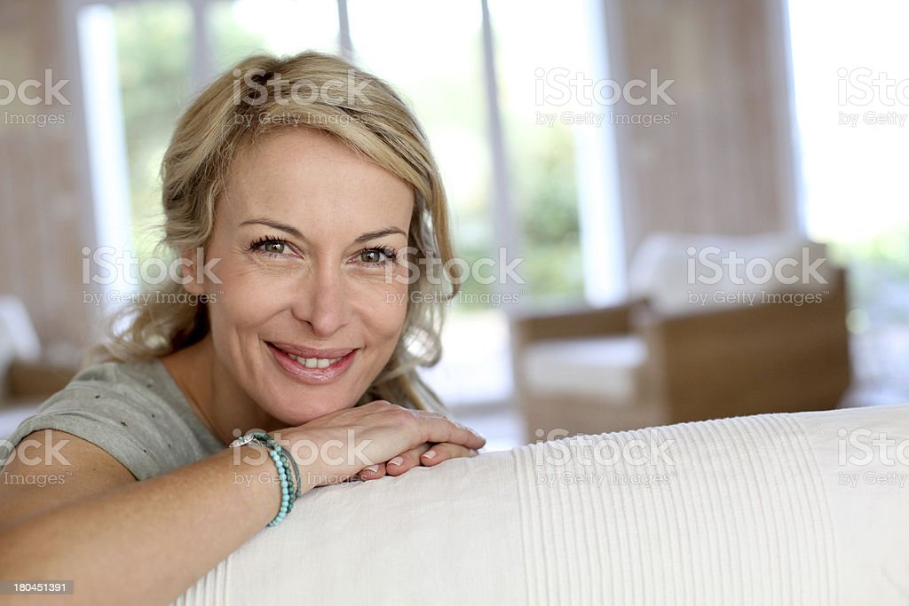 Smiling blonde mature woman sitting on couch royalty-free stock photo