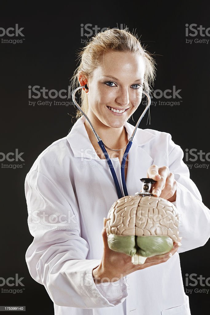 Smiling blonde medical professional examines model brain with stethoscope stock photo