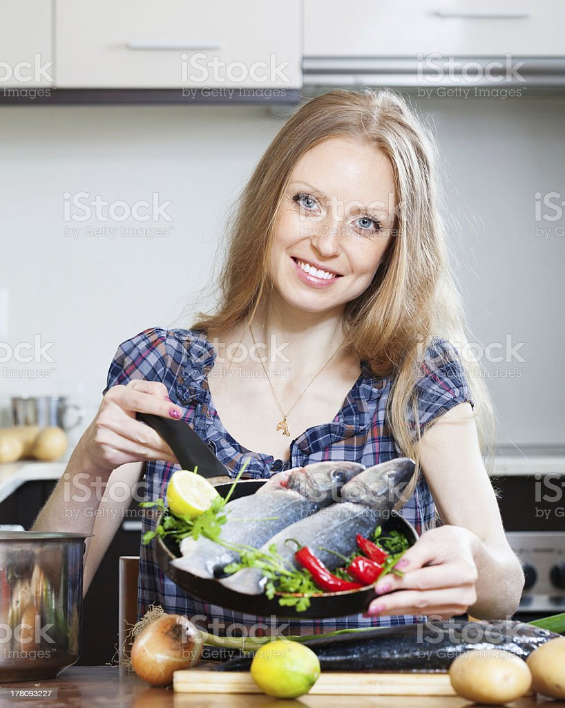 Smiling blonde woman cooking lubina  in frying pan royalty-free stock photo