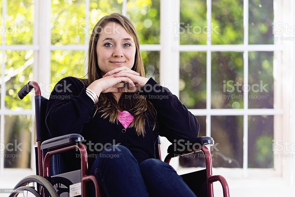 Smiling blonde woman in wheelchair, head propped on her hands stock photo