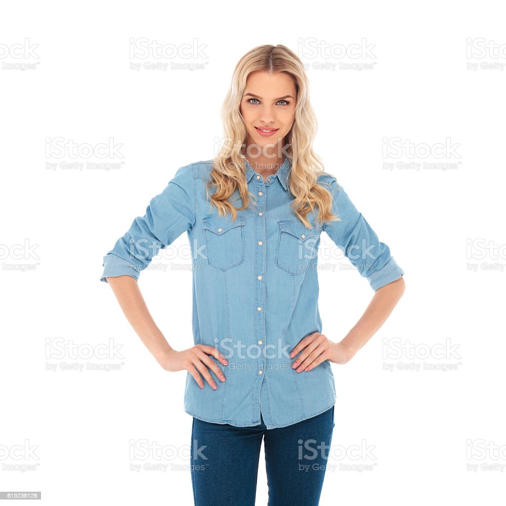 smiling blonde woman standing with hands on waist stock photo