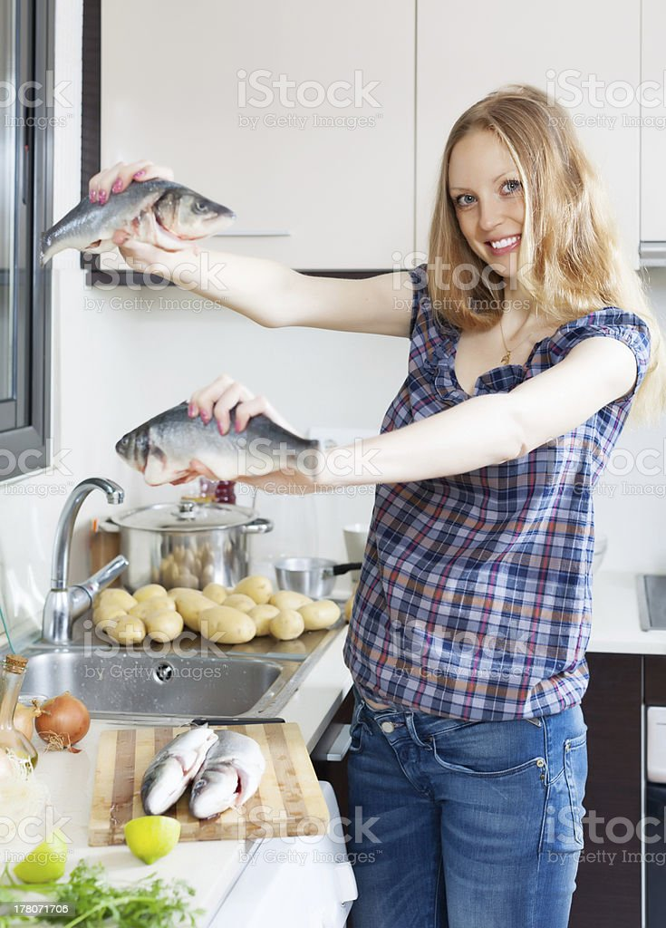 Smiling blonde woman with seabass fish royalty-free stock photo