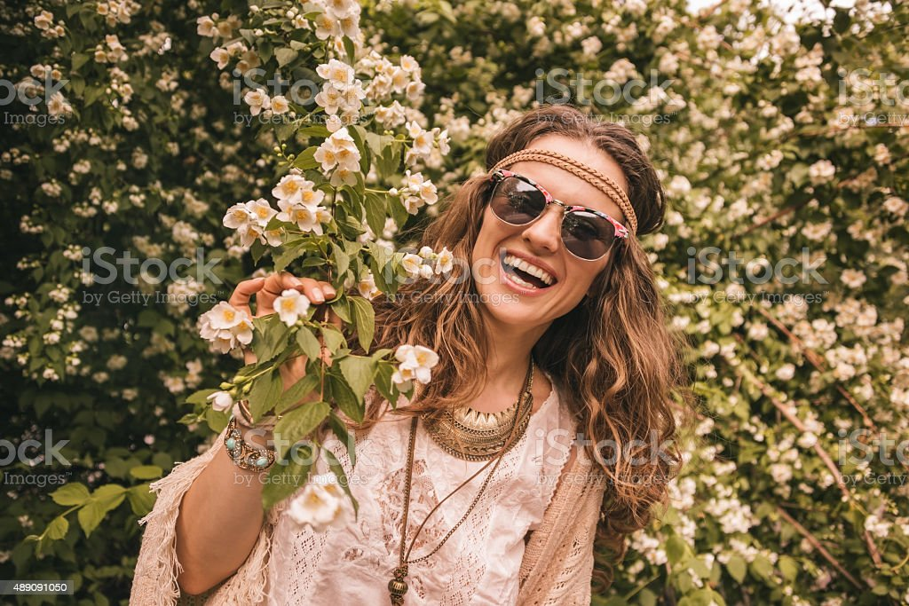 smiling bohemian young woman holding branch of flowers stock photo