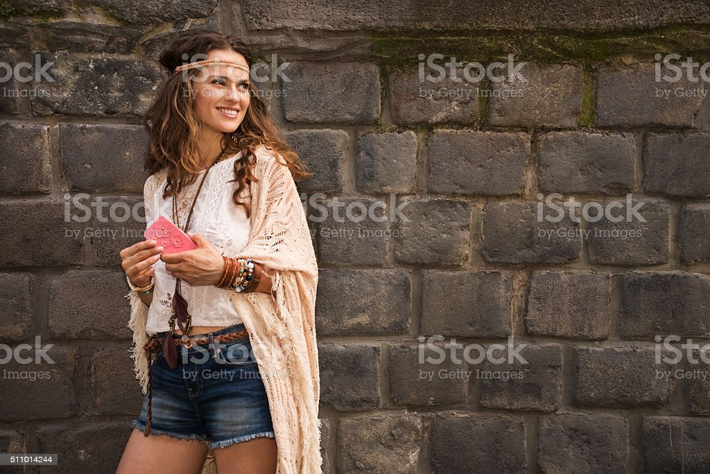 Smiling boho woman near stone wall looking on copy space stock photo