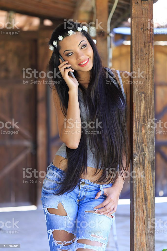 Smiling boho woman with wreath talking on the phone stock photo