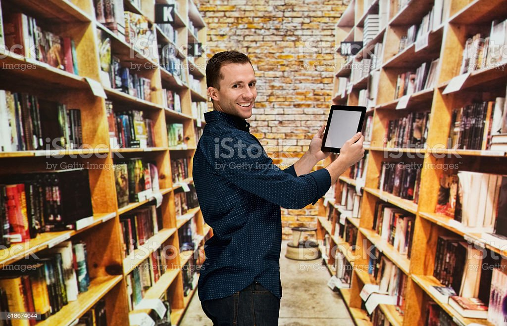 Smiling bookseller holding tablet in bookstore stock photo