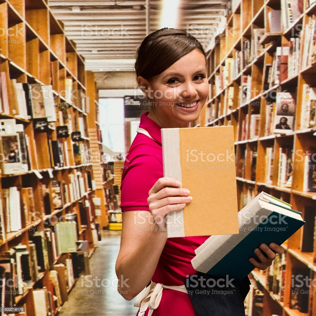 Smiling bookseller in library stock photo