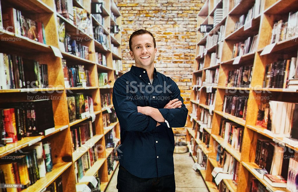 Smiling bookseller standing in library stock photo