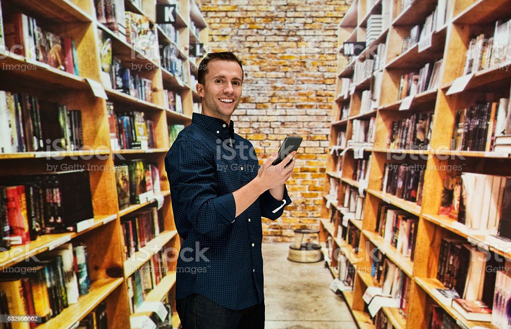 Smiling bookseller using phone in bookstore stock photo