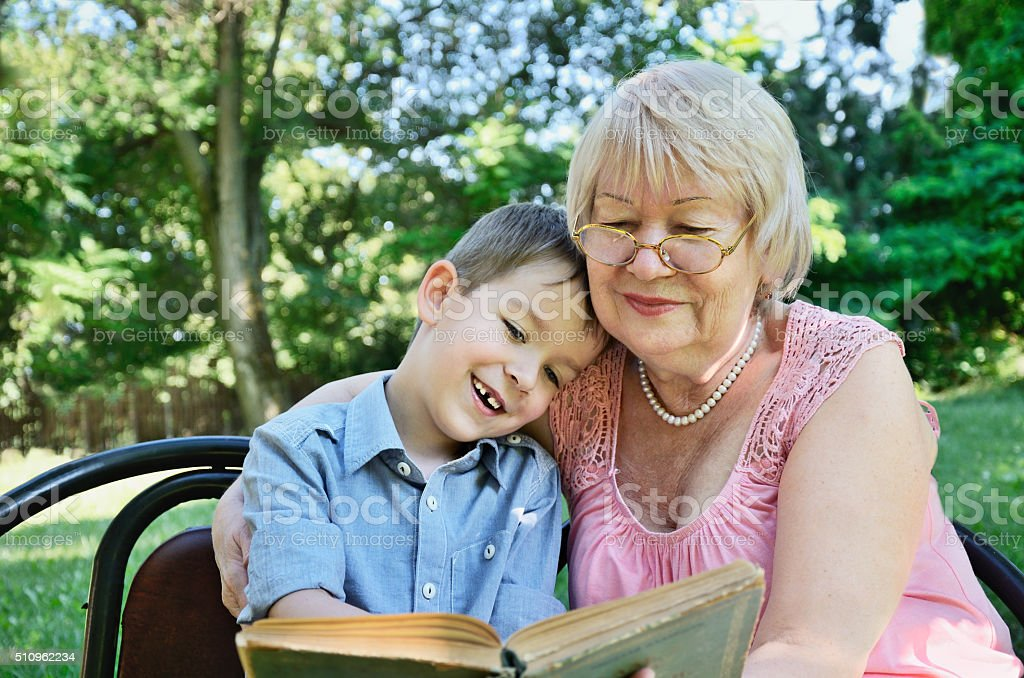 smiling boy and his grandmother sitting in the park stock photo