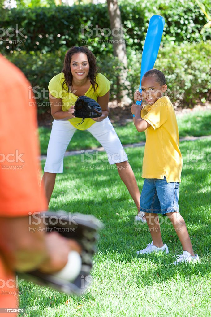 Smiling boy and mother playing baseball with father outdoors stock photo