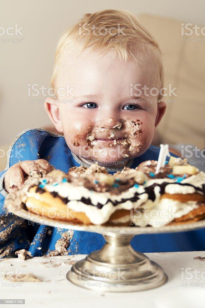 Smiling boy eats a big cake stock photo