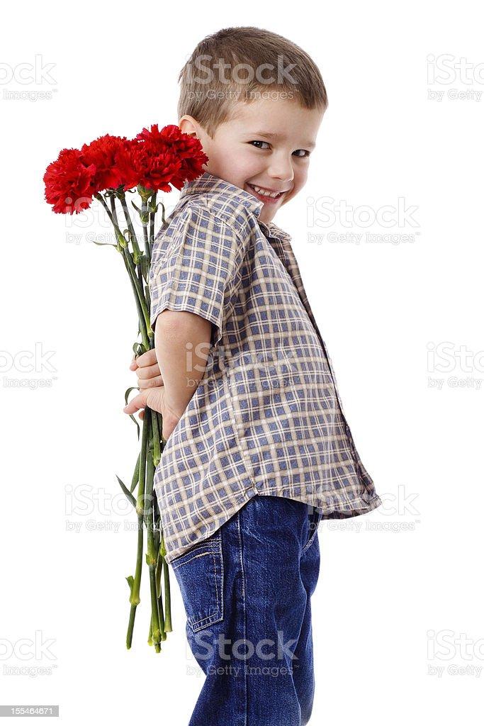 Smiling boy hiding a bouquet stock photo