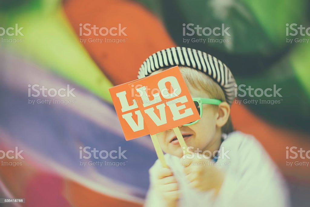 Smiling boy holding a placard with love inscription stock photo