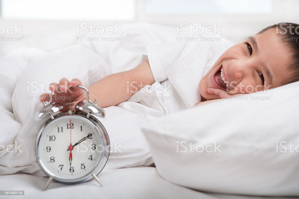 Smiling boy holding alarm clock in bed royalty-free stock photo