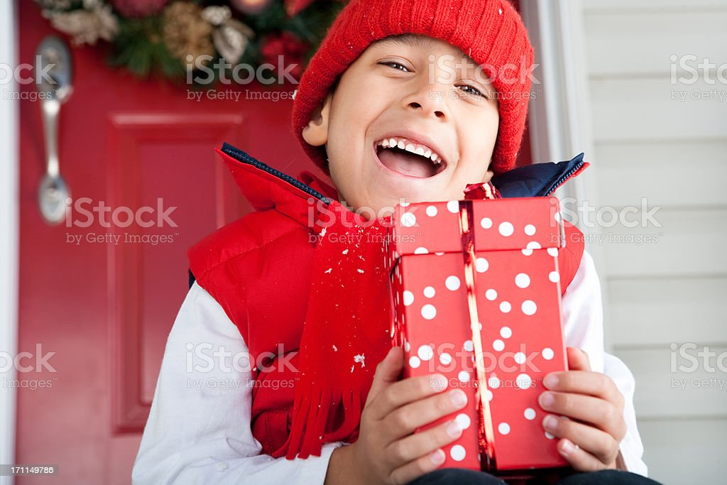 Smiling boy holding christmas present royalty-free stock photo