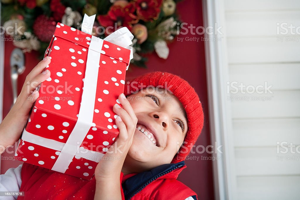 Smiling boy holding christmas present royalty-free stock photo