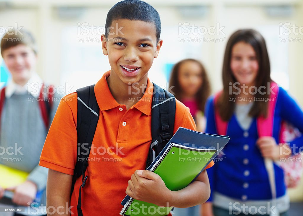 Smiling boy holding files and books at school royalty-free stock photo