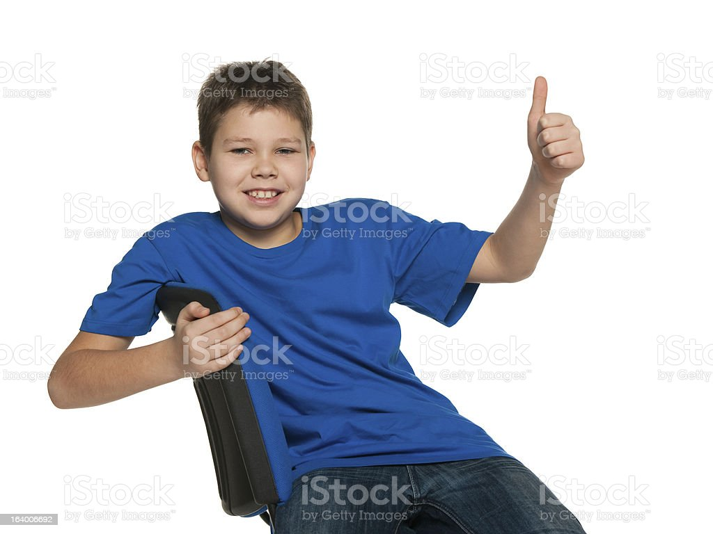 Smiling boy in blue shirt holding his thumb up royalty-free stock photo