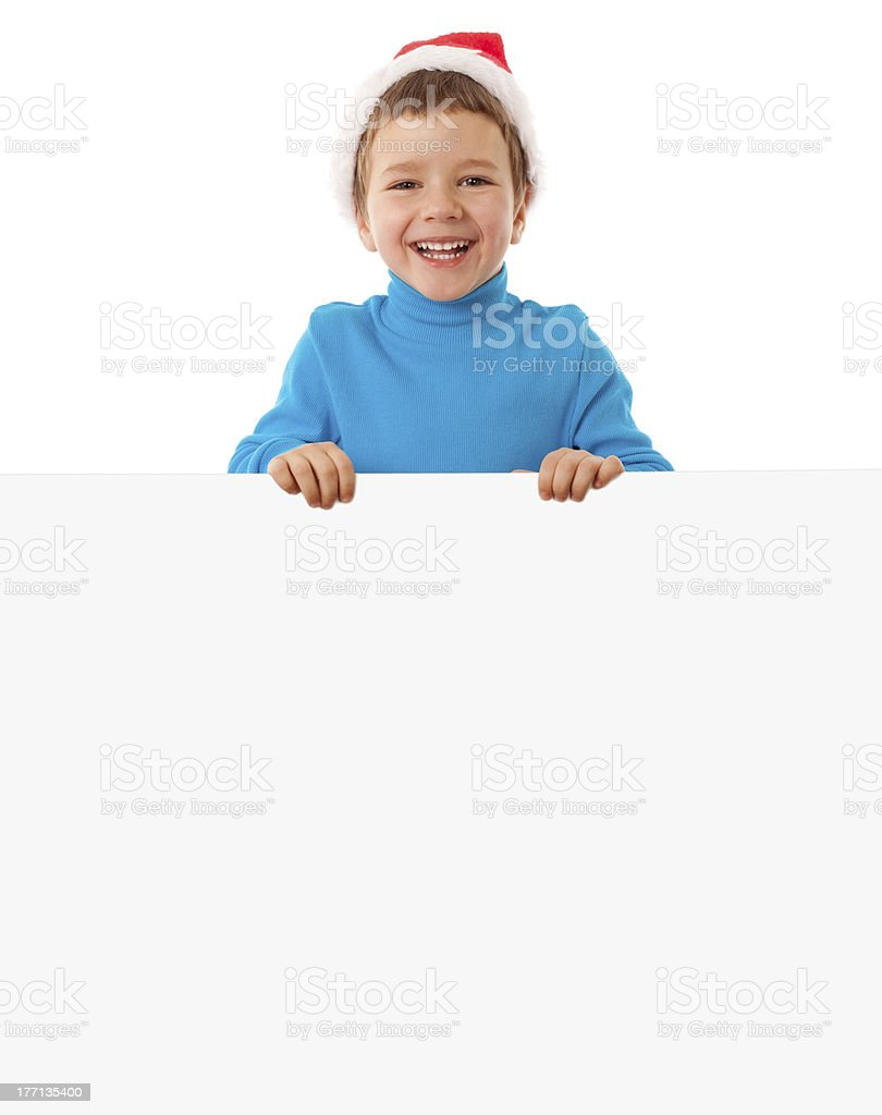 Smiling boy in Santa hat with empty banner royalty-free stock photo