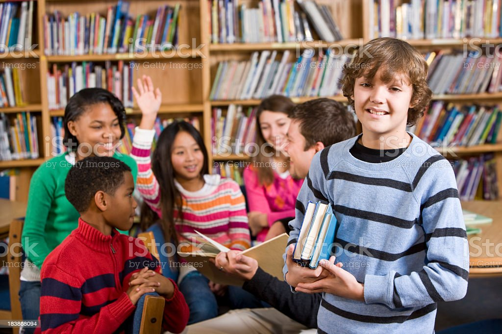 Smiling boy in school library holding books by reading group royalty-free stock photo