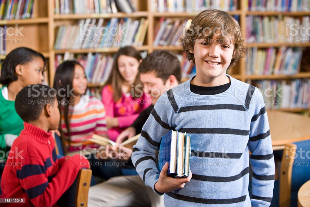 Smiling boy in school library holding books royalty-free stock photo
