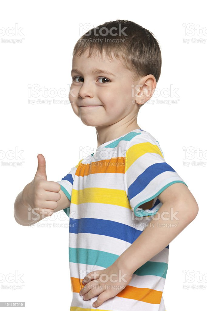 Smiling boy in striped shirt holding one thumb up stock photo