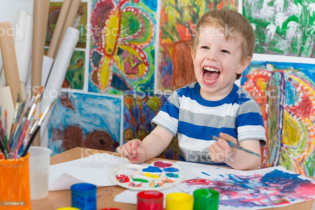 A smiling boy painting in a studio stock photo