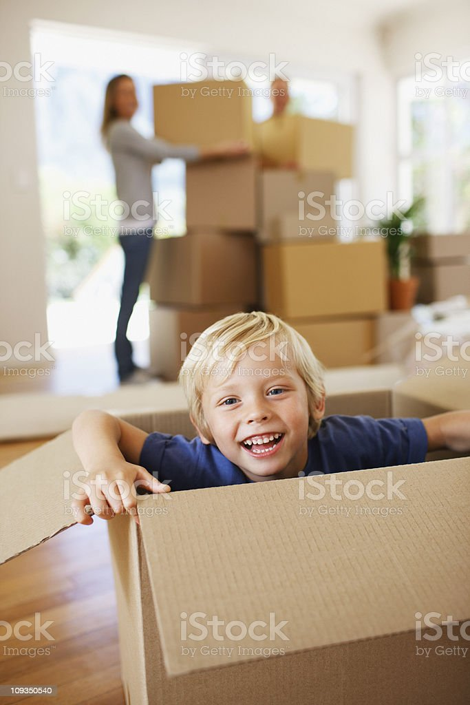 Smiling boy playing on box in new house royalty-free stock photo