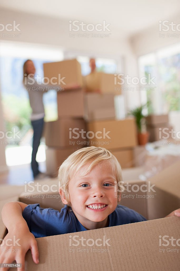 Smiling boy playing on box in new house stock photo