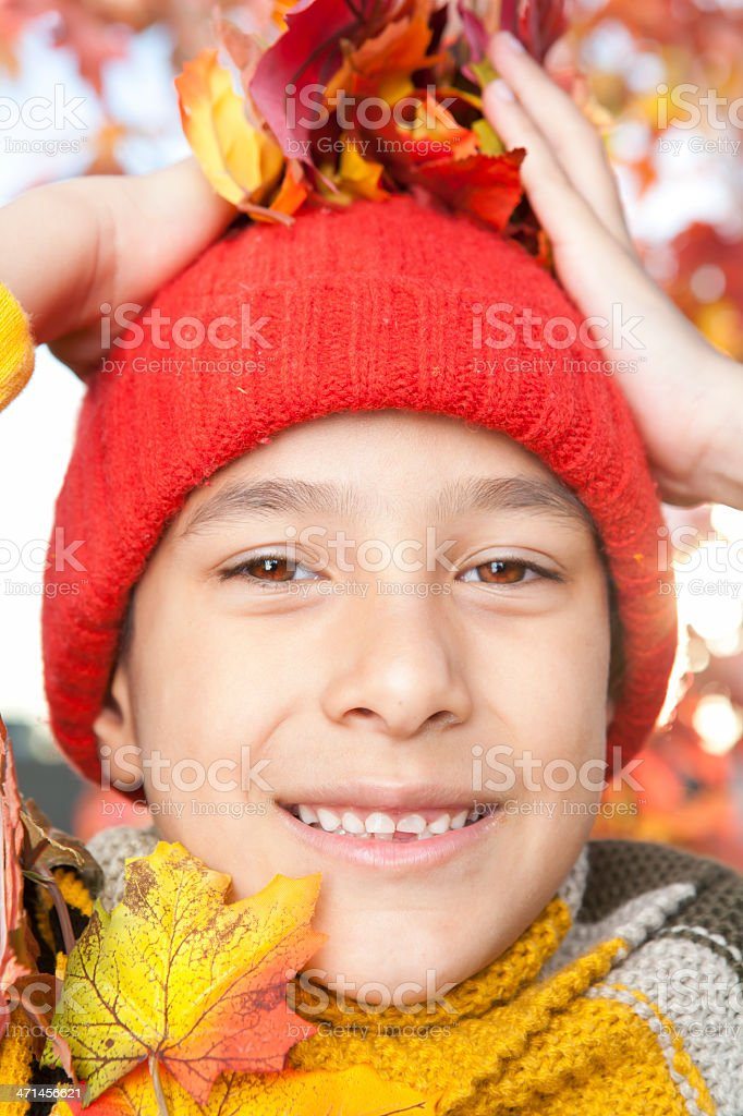 Smiling boy playing with autumn leaves royalty-free stock photo