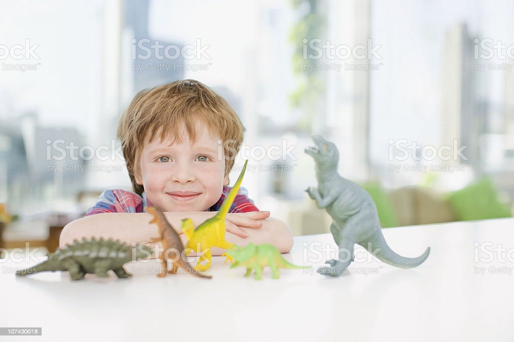 Smiling boy playing with plastic dinosaurs stock photo