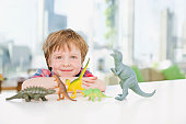 Smiling boy playing with plastic dinosaurs