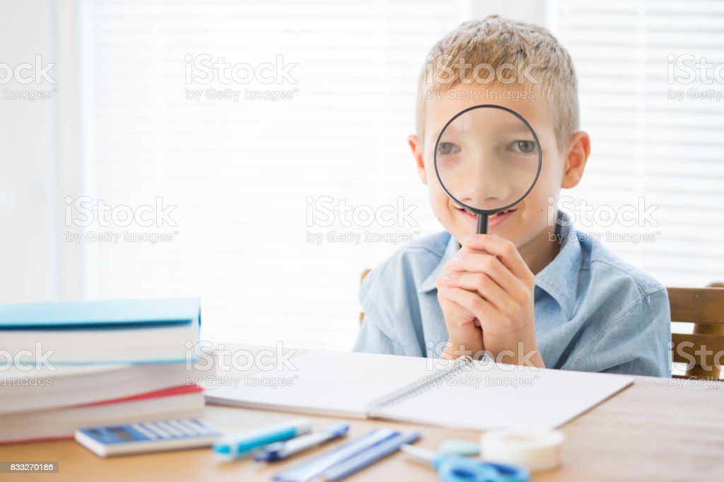 Smiling boy posing with a loupe stock photo