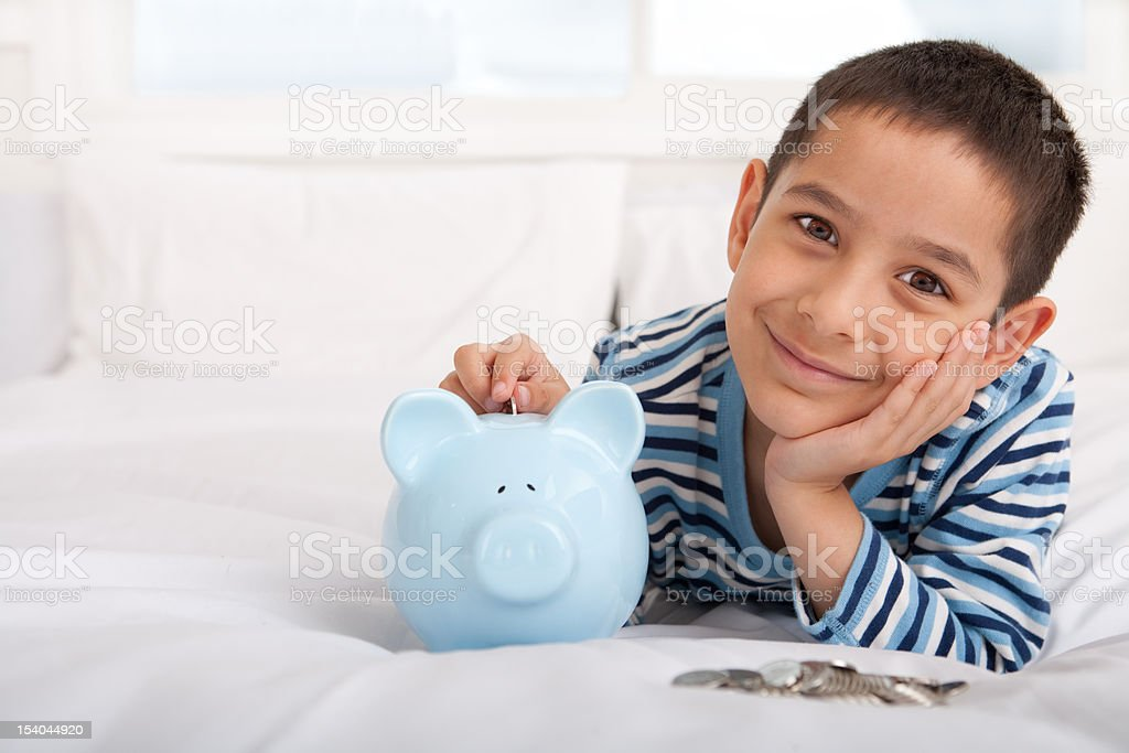 Smiling boy putting money in piggy bank royalty-free stock photo