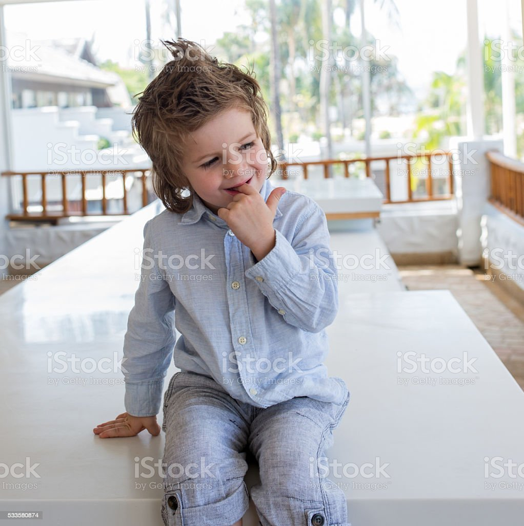Smiling boy relaxing on the table and thinking of something. stock photo