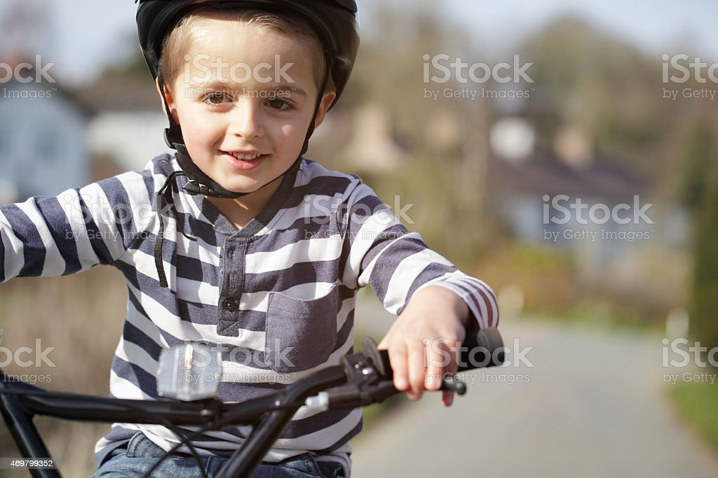 Smiling boy riding a bike with a blurred background stock photo