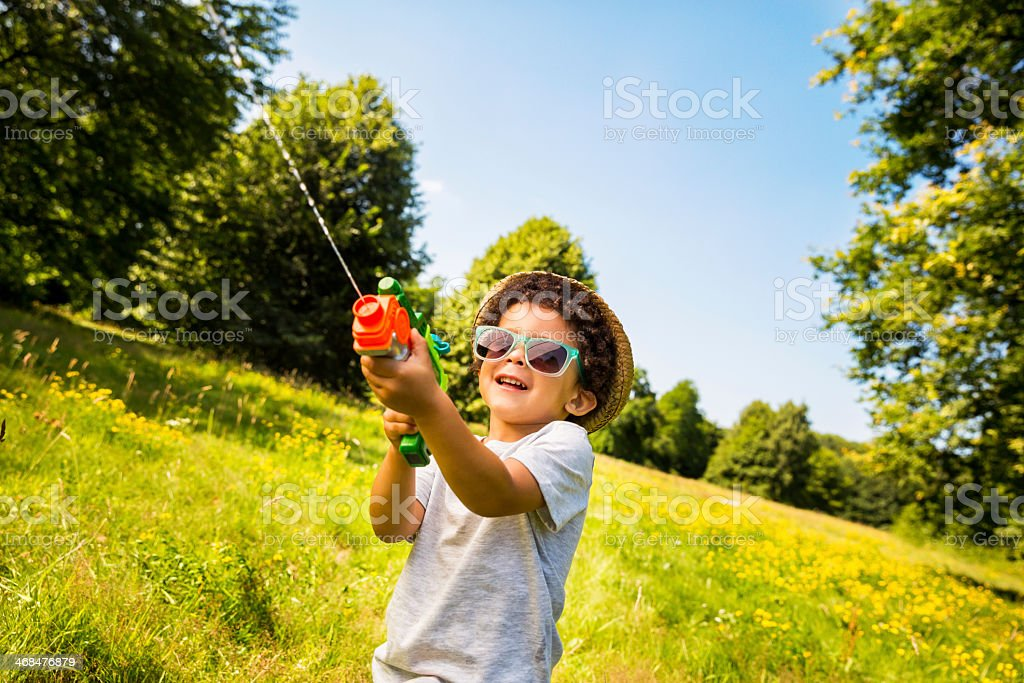 Smiling boy shooting water with squirt gun royalty-free stock photo