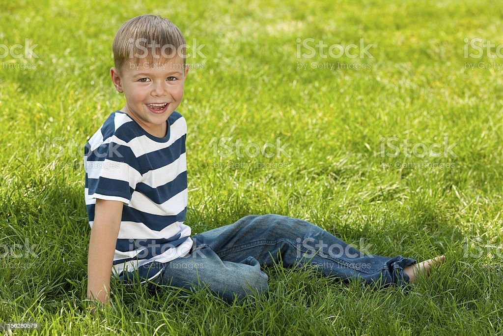 Smiling boy sits in the summer park royalty-free stock photo