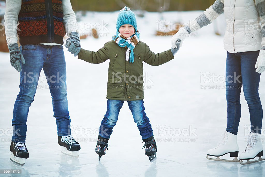 Smiling boy skating with parents stock photo