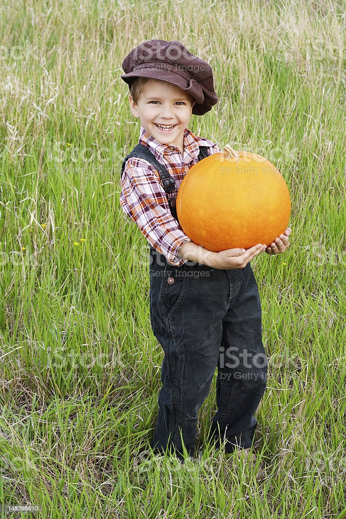 Smiling boy standing with pumpkin royalty-free stock photo