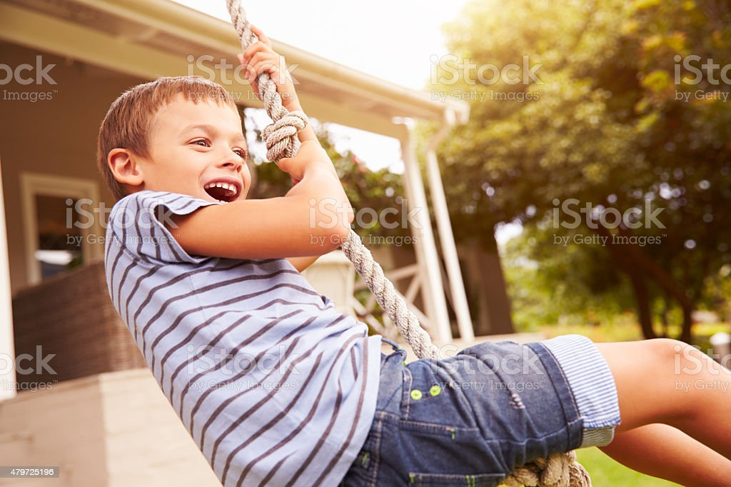 Smiling boy swinging on a rope at a playground stock photo